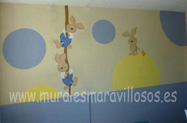 Tres conejitos pintados en pared con círculos de colores